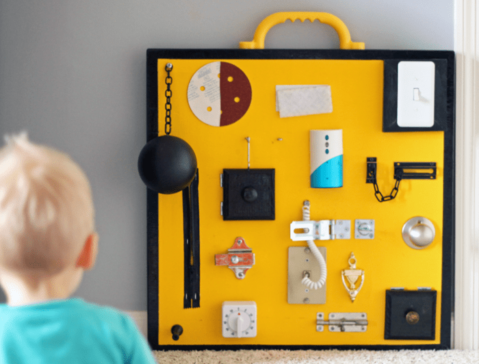 This cool and colorful board consists of a sand paper piece, a piece of velcro, a light switch, costume ball & chain, a swivel hook, an electronic doorbell, a night latch, a zipper, cabinet samples, a twist latch, a door knob, a sliding latch, a phone cord, a door knocker, a door stop, a timer and a gate lock. (via wherethesmileshavebeen)