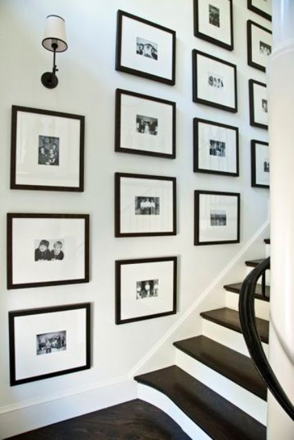 Kaufman Residence, decorated by Phoebe Howard, framed christmas card pictures on stairs----- Over a dozen black-and-white framed Christmas cards are hanging on wall over staircase.