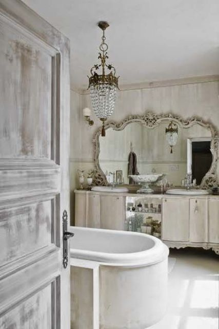 shabby chic bathroom with an oversized vintage mirror and a crystal chandelier