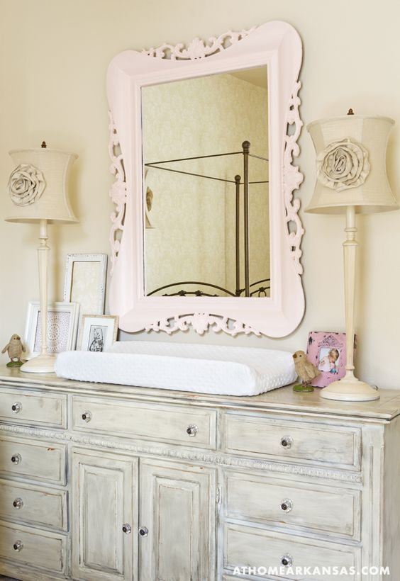 distressed grey changing table with a blush framed mirror