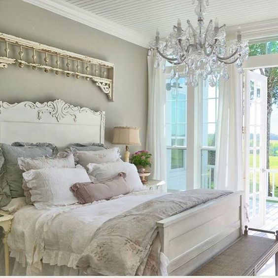 pastel-colored shabby chic bedroom with a crystal chandelier