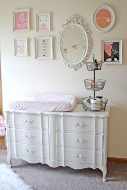 white vintage changing table with white framed gallery wall