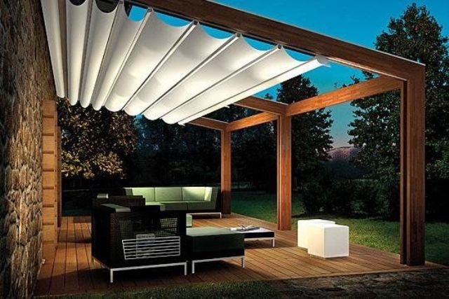 pergola built to the back of the house with a fabric ceiling cover