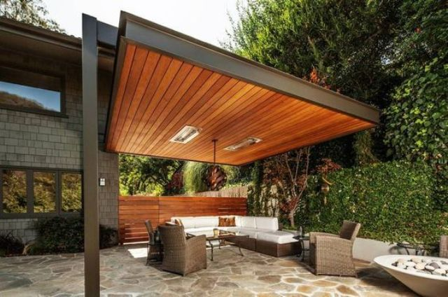 modern wood pergola built to one of the house's walls with a living room