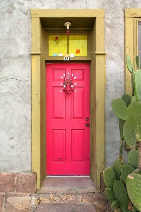 fuchsia front door with a gilded frame