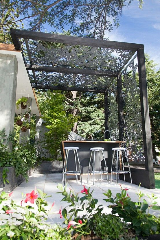 pergola outdoor kitchen at the back of the house decorated with laser-cut screens