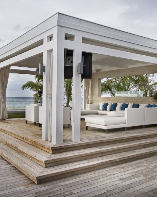 luxurious white cabana with flowing curtains on every side and a cozy and inviting white sectional decorated with alternating white and turquoise throws