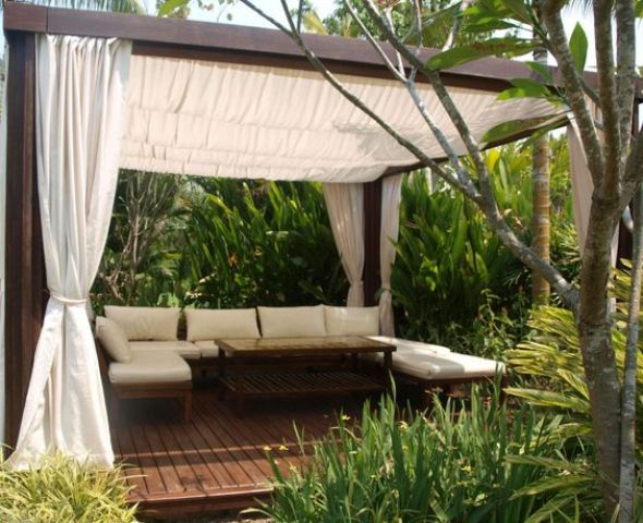 outdoor lounge with a canopy and curtains