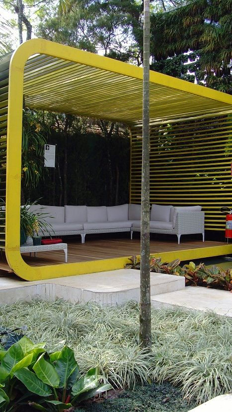 bold yellow pergola with walls and a ceiling suncreens