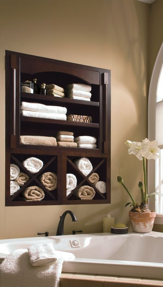 Awesome creative dark stained niche towels cabinet over the bathtub