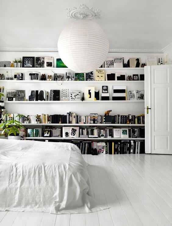 17 open shelves along the whole bedroom wall