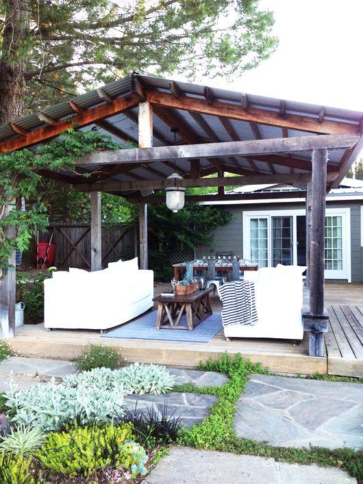 rustic gazebo with a gabled roof and a living and dining space under it