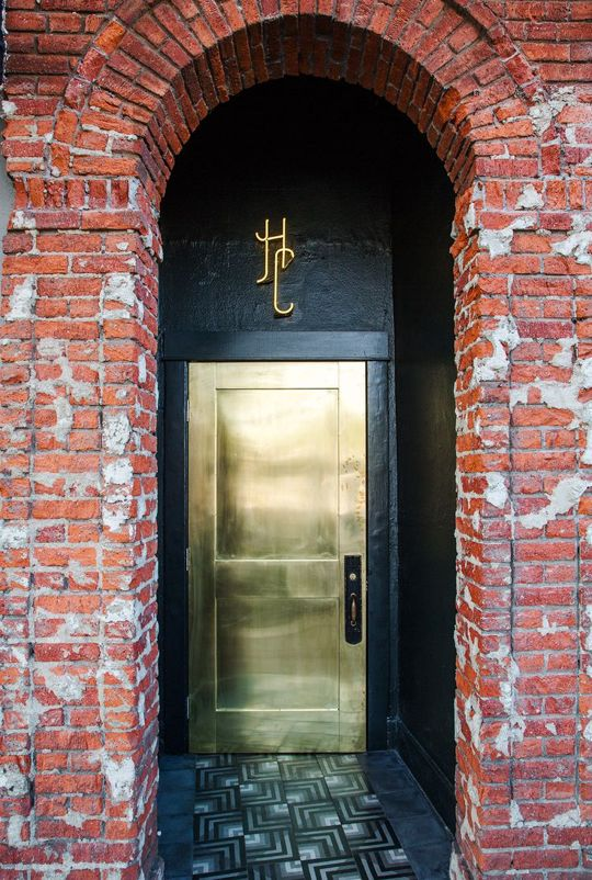 brass finish metal front door with a black entry