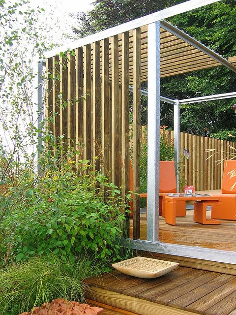 minimalist gazebo of wood and metal with orange furniture