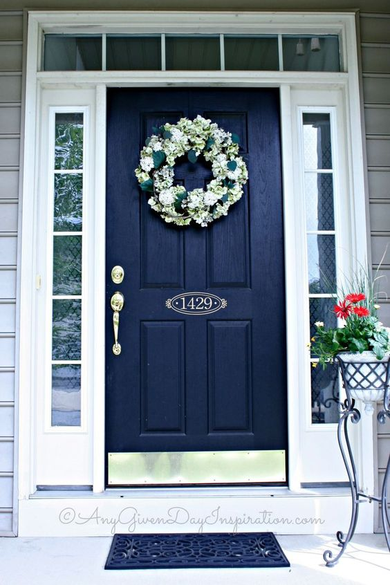 weathered navy front door with white decor