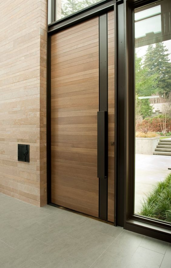 wood-clad modern front door with a black steel strip and handle