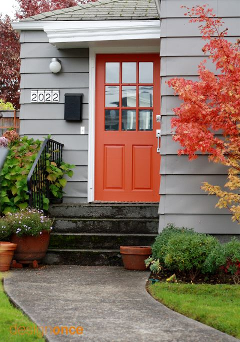 bold orange front door and a tree with orange leaves