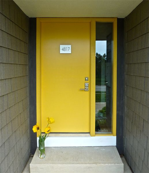modern yellow front door with a glass sidelight