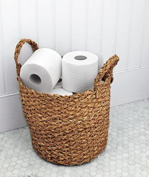 a woven basket holds an ample supply of toilet paper