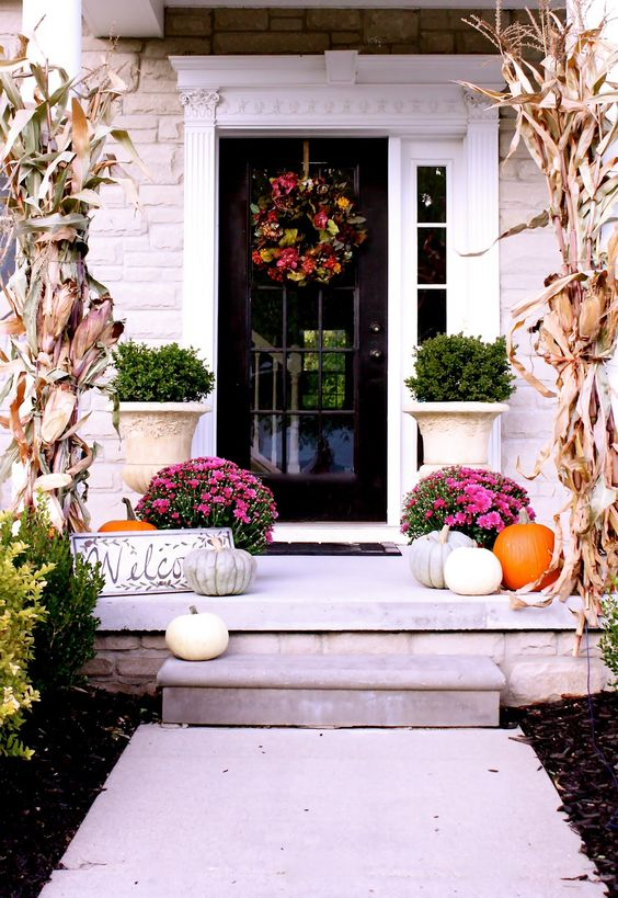 bold fall porch with corn husks, pink flowers and various pumpkins