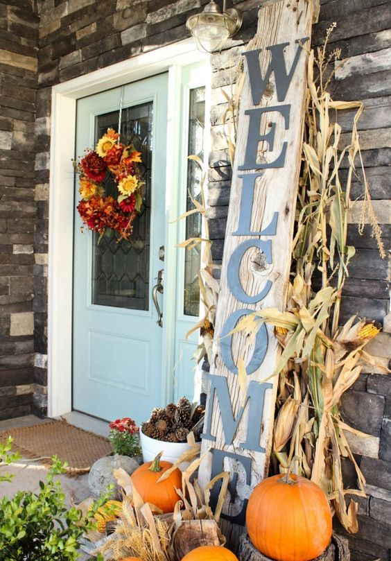 pumpkins on top of chopped logs to create height and dimension, a rustic sign and corn husks