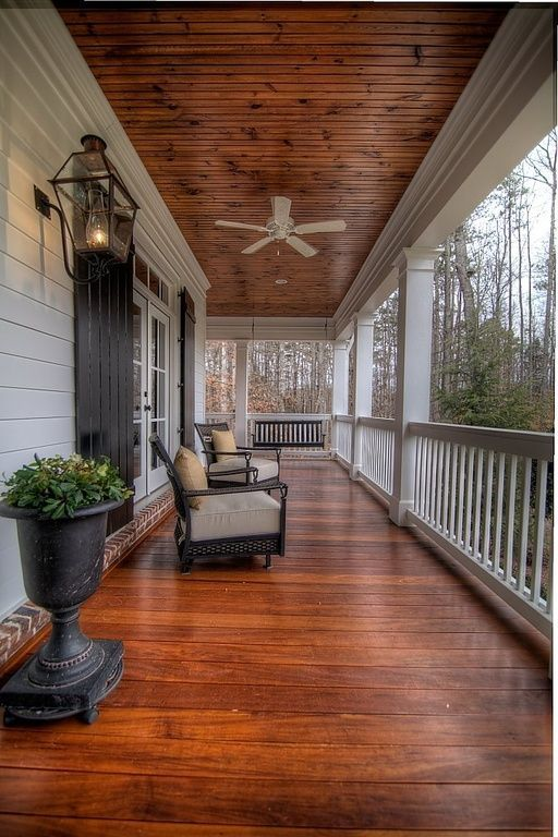 rosewood wraparound porch with chairs and a large planter