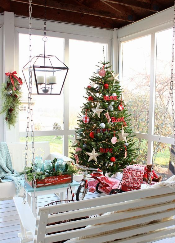 screened porch with a swinging bench and beautiful christmas decor