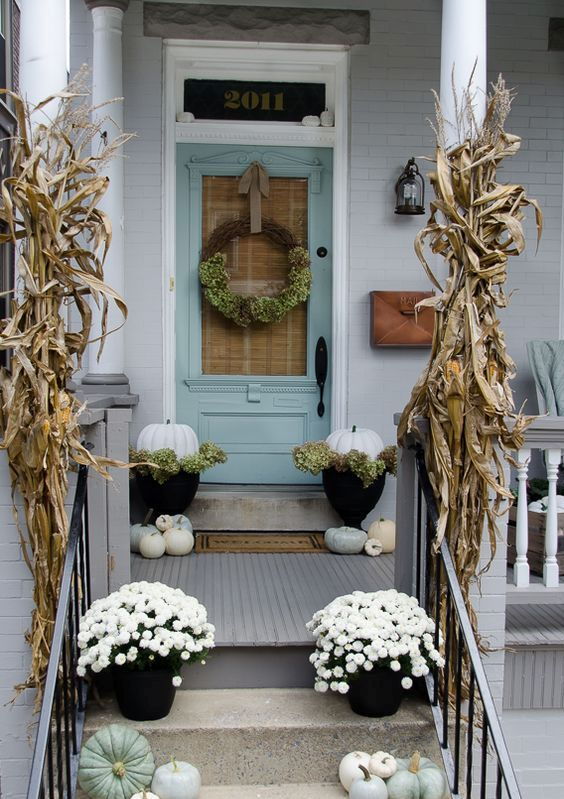 corn husks, white and pale green pumpkins, a wreath and potted flowers