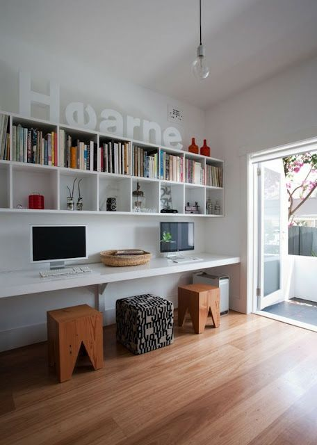 uncluttered study space with a built-in desk and a couple of stools