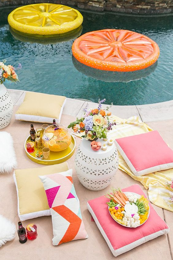 citrus floats in the pool and colorful floor cushions