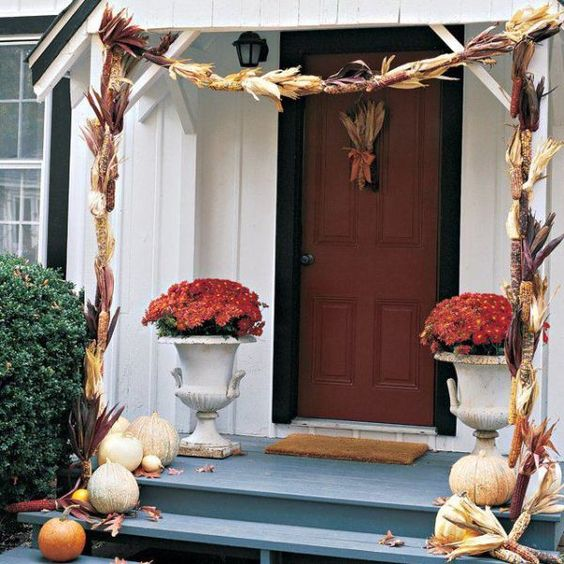 corn stalks over the porch and pumpkins on the steps