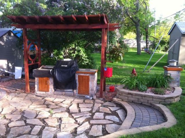 Wood pergola over grill and rock patio