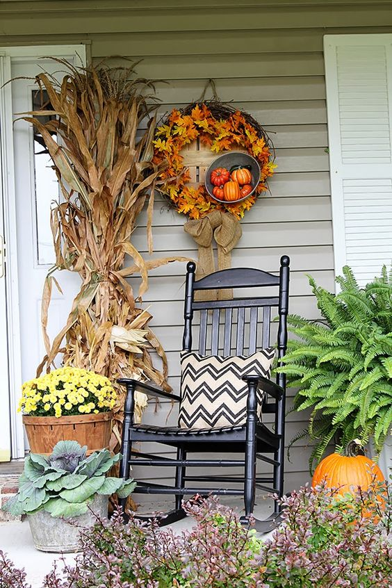 a fall porch decor with cornstalks, a DIY wreath and chevron pillows
