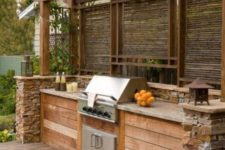 13 built-in grill island with a pergola over it