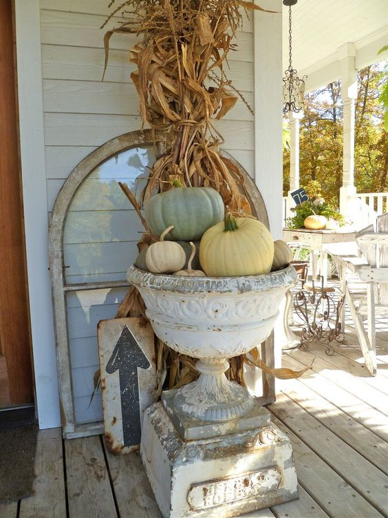 corn stalks and a pumpkin arrangement in a vintage urn