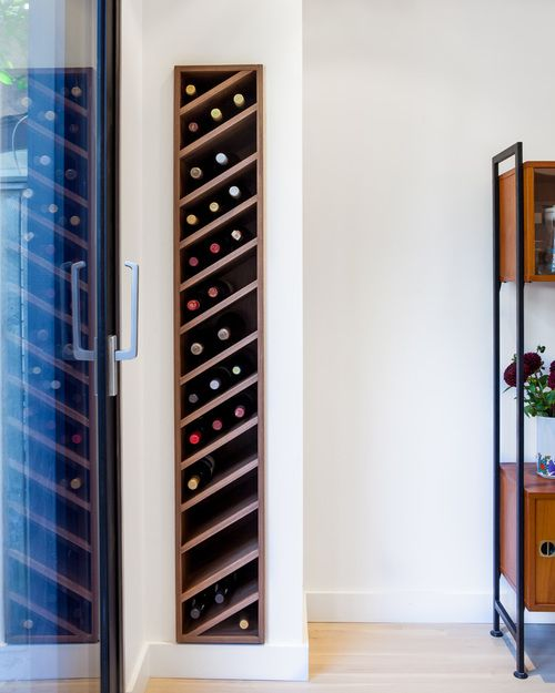 walnut wine rack is slotted discretely into the living room wall