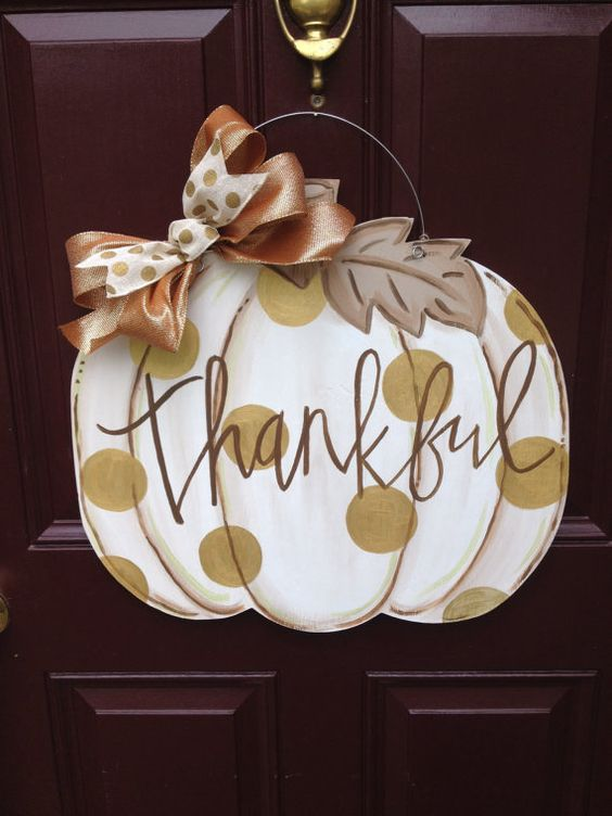white pumpkin door hanger with golden dots