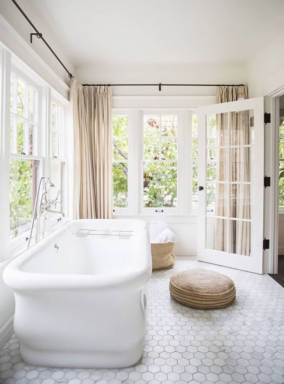 open and airy bathroom with neutral curtians