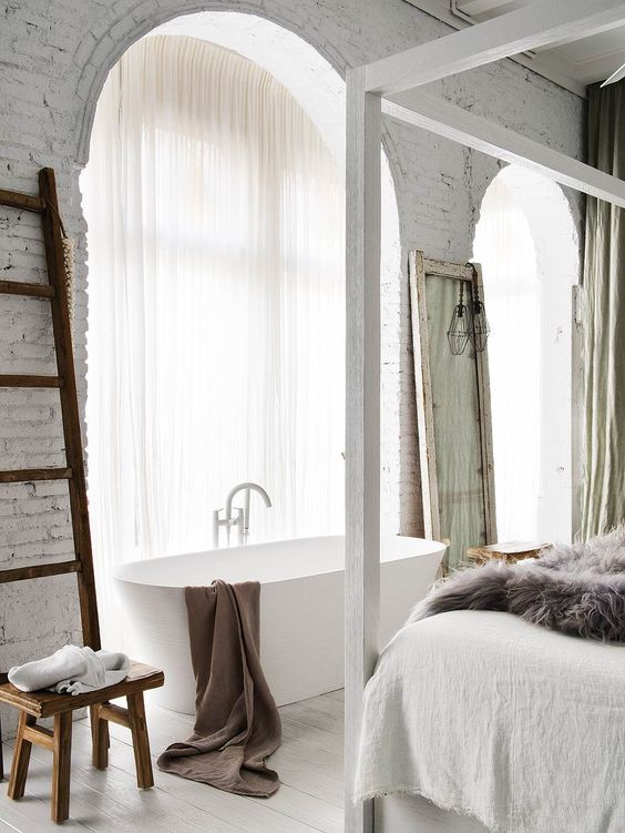 free-standing bathtub and light transparent curtains