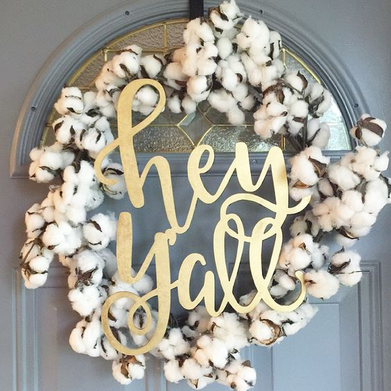 hand-lettered door sign with a cotton wreath around