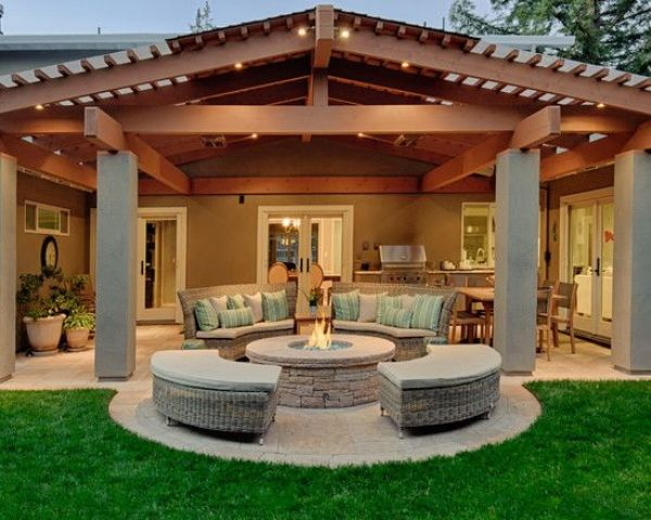 roofed back porch with a fire pit and a conversation area