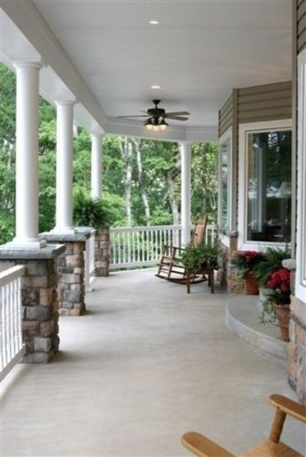 Picture of traditional wrap around porch with rocker chairs for Wrap around porch columns