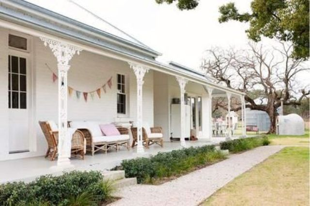white warp around porch with wicker furniture for a relaxed feel