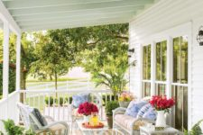 25 roofed porch with white wicker furniture and potted greenery