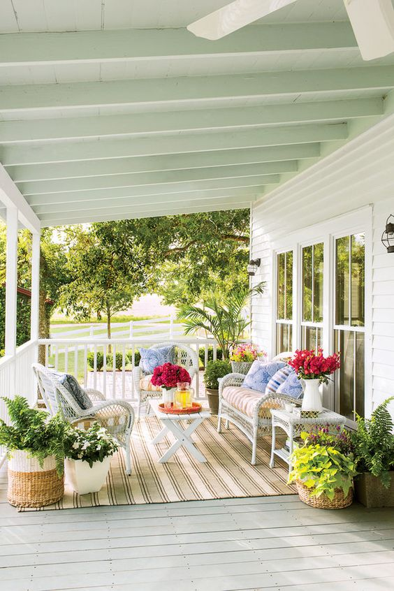 roofed porch with white wicker furniture and potted greenery