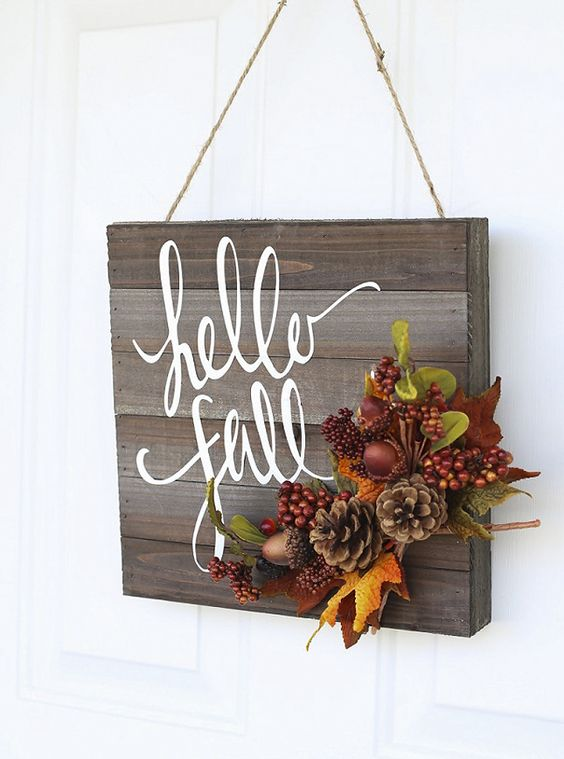 wooden sign decorated with faux berries, leaves and pinecones