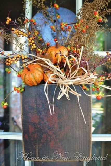 outdoor doorbox stuffed with pumpkins and branches