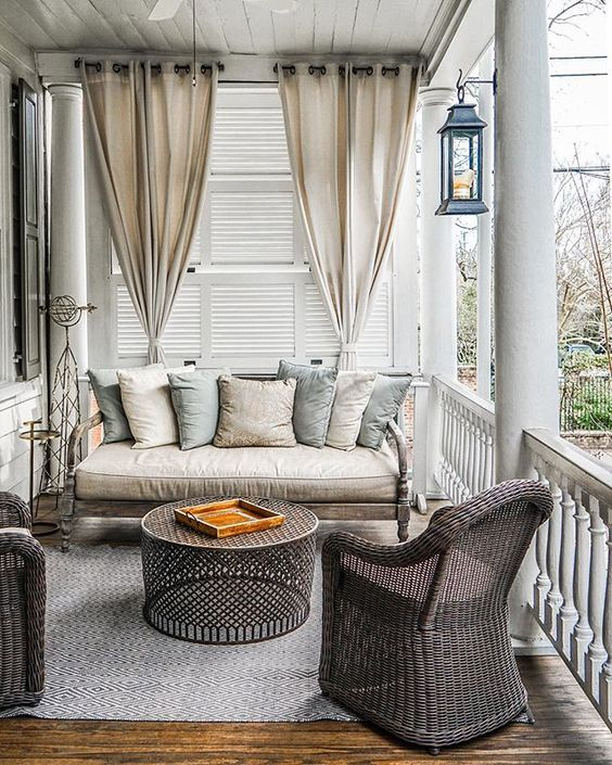 this neutral-colored porch is a cozy reading nook with wicker furniture