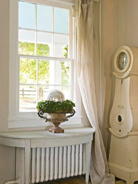 antique table with a distressed white finish sits over the radiator