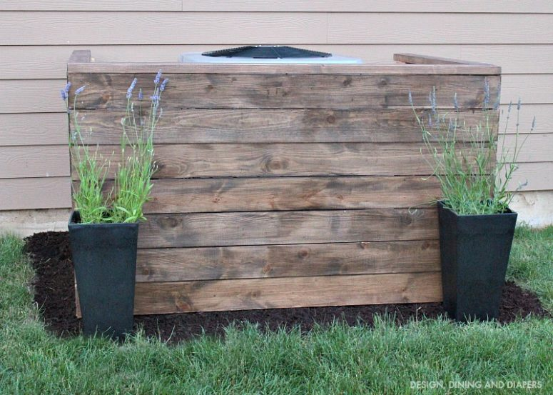 DIY weathered wood AC unit cover with potted flowers (via designdininganddiapers.com)